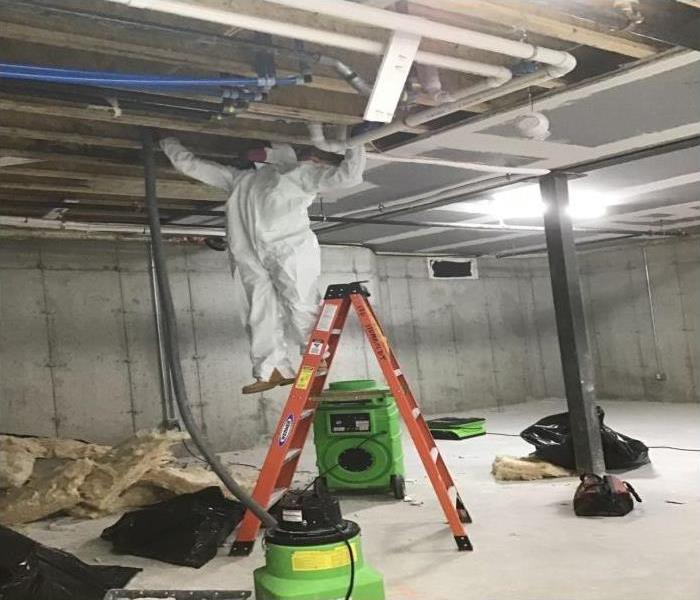 Technician removing insulation from ceiling