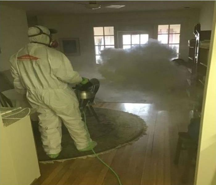 Technicians  in protective suit misting home