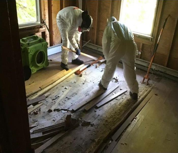 technicians removing rotted flooring