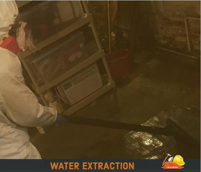 technician in white trecsuit extracts contaminated water from basement